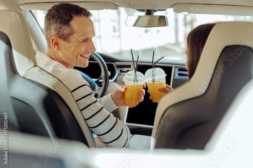 Foto op Plexiglas Sap Joyful positive couple cheering with juice