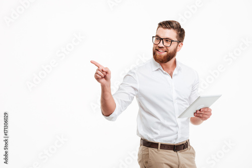 Cheerful young bearded man using tablet computer.