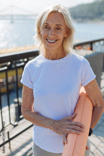 Poster Upbeat senior woman posing with a yoga mat on bridge
