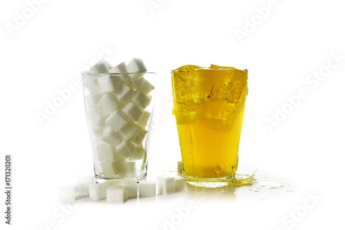 glass full of sugar cubes compared to a glass with a yellow sweet beverage, isol Poster