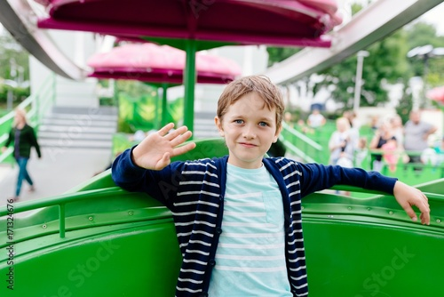 Plakat Happy child boy having fun in amusement park.
