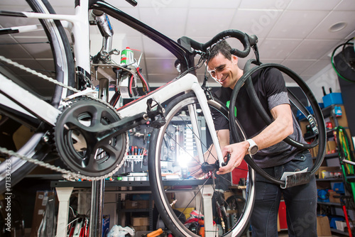 Deurstickers Male involved master is repairing the bicycle in a special workshop