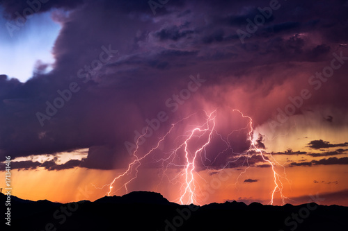 Fotobehang Aubergine Lightning bolts strike from a sunset storm