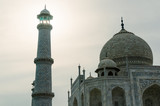 The dome and the tower minar of the Taj Mahal against a sunset. This shows off the architecture of the famous mughal monument