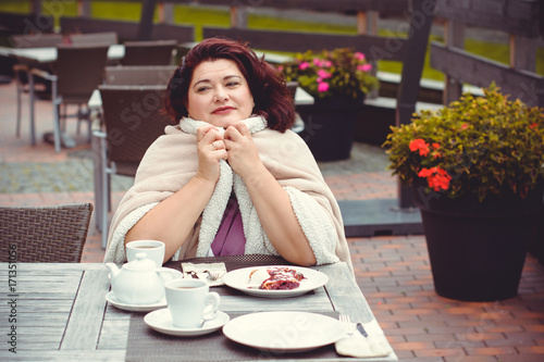 Mature stylishly dressed woman, dark hair eating breakfast tasty sweet cake in a cafe drinking coffee . The beauty of the city's morning. The concept of harmony and life in a big city © tanyaden