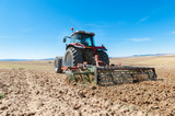 agricultural tractor in the foreground with blue sky background. - 171354402