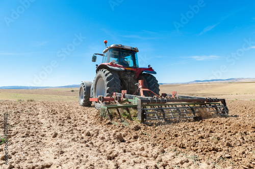 Poster agricultural tractor in the foreground with blue sky background.