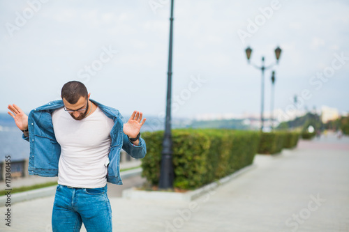 Handsome athletic fit man in jeans wear fitness model outdoors