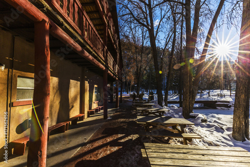 Papiers peints Marron chocolat sun shining over a rustic ski lodge in the winter