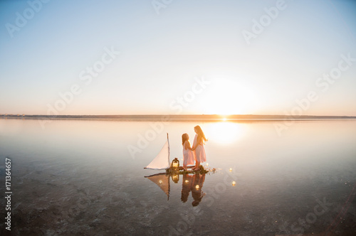 Fotobehang Zeilen Happy girls sail across the lake at sunset and catch the moon and collect the stars