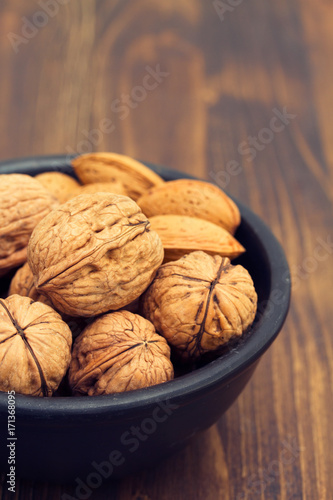 walnuts and almond on black bowl on wooden background