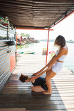fitness instructor assisting young woman in stretching  exercise outdoor - 171368267