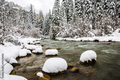 Fotobehang Khaki snow covered rocks in a cold mountain river