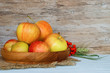 Yellow apples in the plate of wood on a wooden vintage background with empty place for text