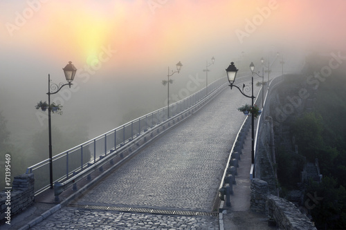 Canvas Kiev Misty morning bridge over the river below the castle in Kamyanets-Podilsky on the background of the dawn mist gentle waves give the romantic charm of the legends of Ukrainian History..