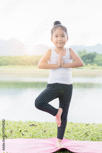 Fotobehang School de yoga Little cute asian girl practicing yoga pose