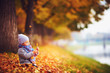 cute little baby girl sitting in autumn fallen leaves