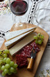 Still life with wine, soft cheese and grapes..