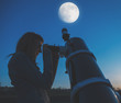 Girl looking at the Moon through a telescope.  - 171408493