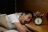 Young man turning off the alarm clock on the bed - 171408401