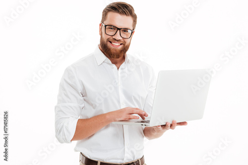 Happy young bearded man using laptop.