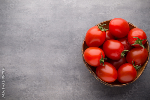 Staande foto Rome Small plum tomatoes in a wooden bowl on a gray background.