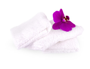 Stack white spa towels on white background  with purple  orchid flower.