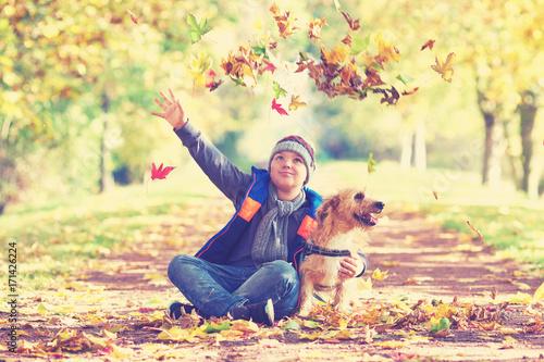 aufgeweckter Junge mit seinem Hund im Herbst Poster
