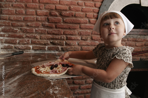 Fotobehang Pizzeria Little girl stretching the pizza up the shovel.
