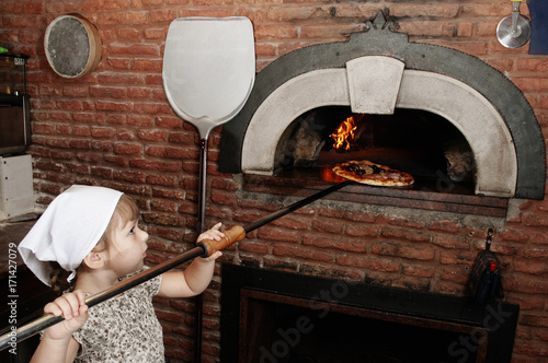 Staande foto Pizzeria Baby baker takes out pizza from the wood-burning stove
