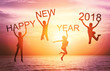 Happy new year card 2018. Silhouette of children girl jump on tropical beach with fantastic sunset sky background. Kids holding the word happy new year and number 2018 with sea and sunrise background.