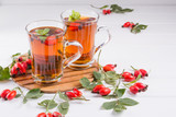 Rose hip tea in transparent cup with honey and fresh berries. Vitamin C drink on white background. - 171439677