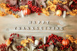 Thanksgiving day autumn background with with Happy Thanksgiving letters, seasonal autumn berries, pumpkins, apples