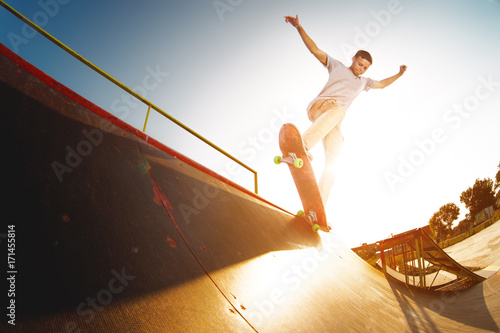 Fotobehang Skateboard Teen skater hang up over a ramp on a skateboard in a skate park