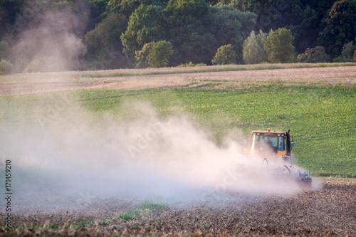 Traktor pflügt Feld im Herbst bei Sonnenaufgang