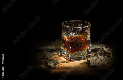 malt whiskey in a glass stands on a wooden board around oak chips
