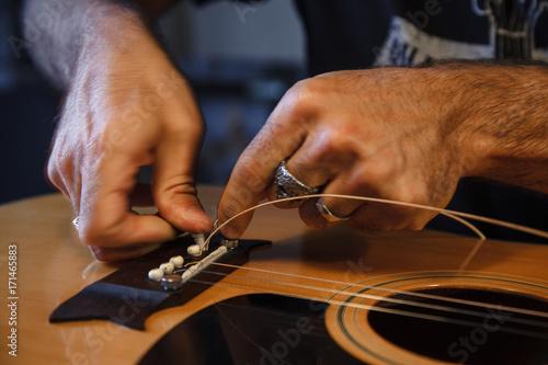 Foto Murales liutaio applica le corde ad una chitarra classica