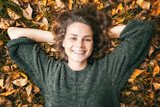 Young beautiful woman lies on autumn foliage in the park - 171467893