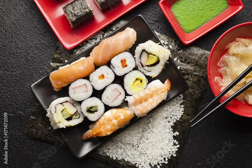 Papiers peints Sushi bar Sushi set on red and black dishes and black table background
