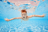 Fototapeta Łazienka - Happy young boy swim and dive underwater, kid breast stroke with fun in pool. Active healthy lifestyle, water sport activity and lessons with parents on summer family vacation with child © biotin