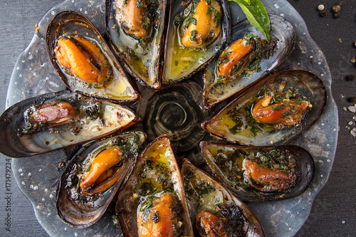Mussels baked with butter and parsley in shell mussels. Lemon, parsley and spices around plate on dark background. - 171479234