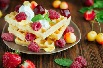 Belgian waffles with berries, whipped cream and grated chocolate