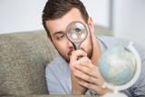 man looking at the globe using a magnifying glass - 171481812