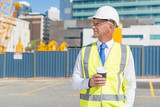 Engineer builder on construction site at sunny day with coffee in hand - 171485205