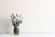 Lavender in glass jar on white table against neutral wall background with copy space
