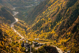 Main highway in Andorra bends and turns, near the Meritxell chapel, through a valley, at the peak of fall foliage colors - 171509010