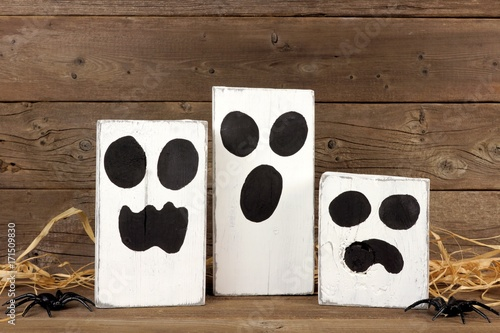 Rustic wooden Halloween ghosts against an aged wood background Poster