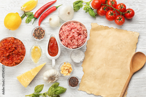 Fotobehang Kruiden 2 Composition of raw meat with vegetables and paper on wooden background