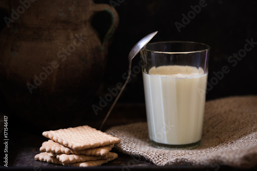 Foto op Plexiglas Milkshake Glass of fresh farm milk with butter cookies stack on sack cloth and spoon by side, rural scene in rustic style and dark background with clay pot, organic breakfast, diary product, copy space for text