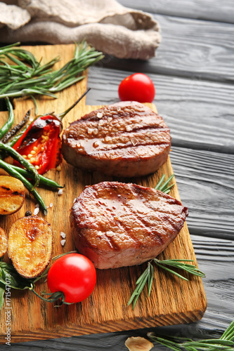 Composition with delicious steaks and vegetables on wooden table - 171547073
